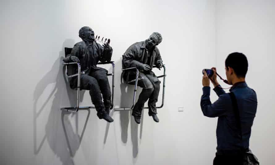 A man takes a photo of Spanish sculptor Juan Muñoz's 'One Laughing at the Other' at Art Basel in Hong Kong