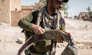 A member of the Asa'ib Ahl al-Haq militia carefully handles a seized Isis suicide belt found in Ba'aj, northern Iraq.