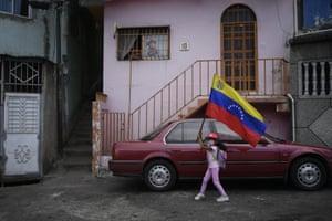 Caracas, Venezuela: a girl flies a Venezuelan flag on the anniversary of the 1992 failed coup attempt by Hugo Chavez