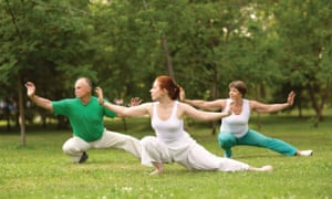Two women and a man practising Tai-chi.