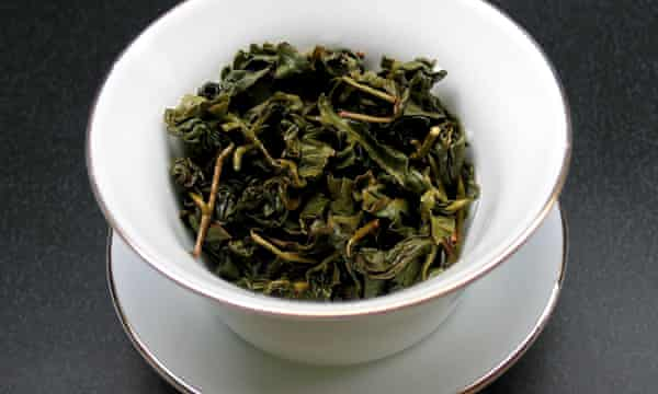Dry leaves of green tea in a cup