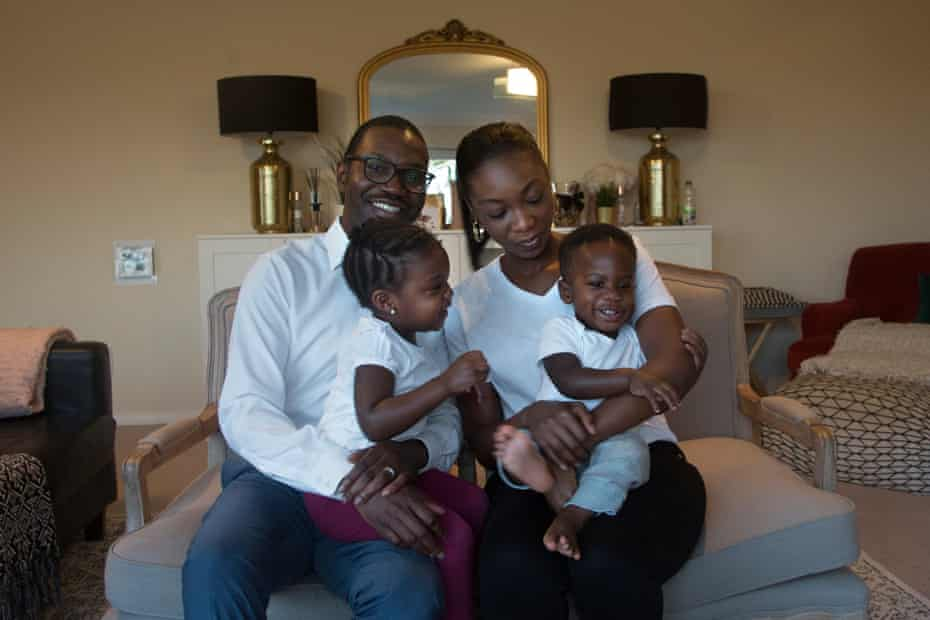 Robert and Ayooluwa hold daughter Forefulowa, 3, and son Folajimi, 1, on their laps at home in London