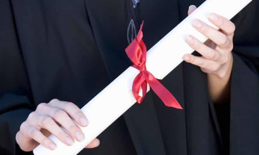 A graduate holding a degree certificate scroll
