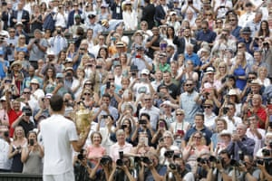 Federer shows the trophy to the Centre Court crowd.