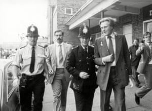 Police lead Michael Heseltine away from the Moss Lane community centre in Croxteth, Liverpool, in August 1982.