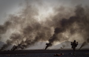 Helmand province, 2011. A US marine walks to pick up food supplies dropped from a plane by parachutes outside Forward Operating Base Edinburgh.