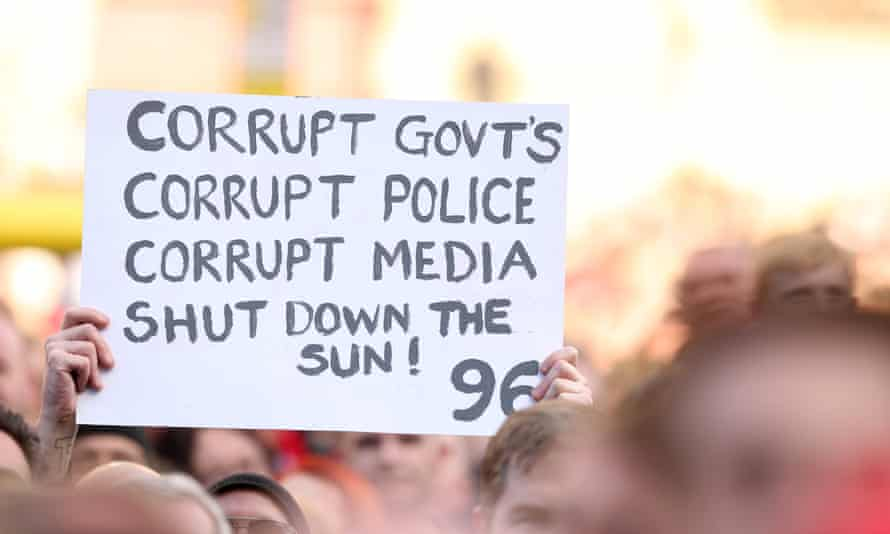 A Liverpool fan holding up a sign saying 'corrupt governments, corrupt police, corrupt median – shut down the Sun'