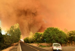 A plume of smoke rises as impending flames from the 'wall fire' approaches Forbestown Road near Oroville. The first major wildfires after the end of California's five-year drought raged across the state