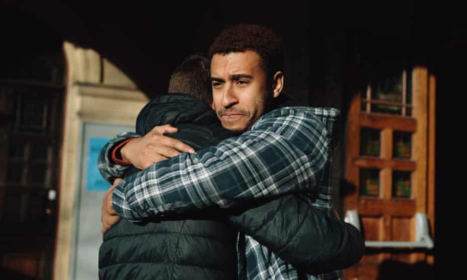 Two men huggingTwo men hug outside of a building