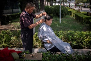 A man gets a haircut on the street in Beijing, China