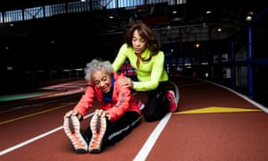 Ida Keeling sitting on a race track in kit, bending forward and holding the toes of her trainers, with her daughter behind her, kneeling and with her hands on her mum's shoulders