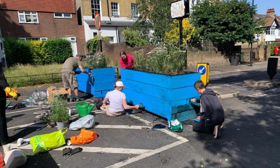 People repaint a planter that was covered in oil in Lambeth