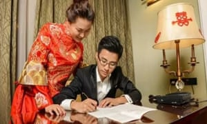 Li Yunpeng and his bride, Chen Xuanchi, write out the Communist party constitution