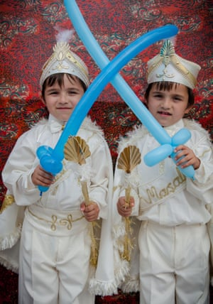 Two young boys in their costumes hold balloon swords