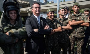 Jair Bolsonaro, who won the first round of Brazil's presidential election on Sunday, posing with militaries during a military event in Sao Paulo, Brazil in May.