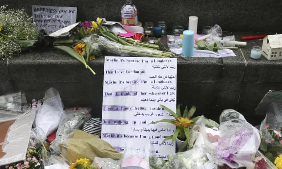 A sign, in Arabic and English, is placed before flowers at a memorial in Potters Field Park, London.