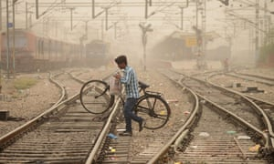 An Indian commuter crosses railway tracks as dust covers sky in Jalandhar.