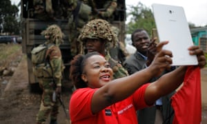 A woman and a man take selfies with soldiers