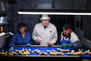 Boris Johnson helps quality control workers during a general election campaign visit to the Tayto Castle crisp factory in County Armagh.