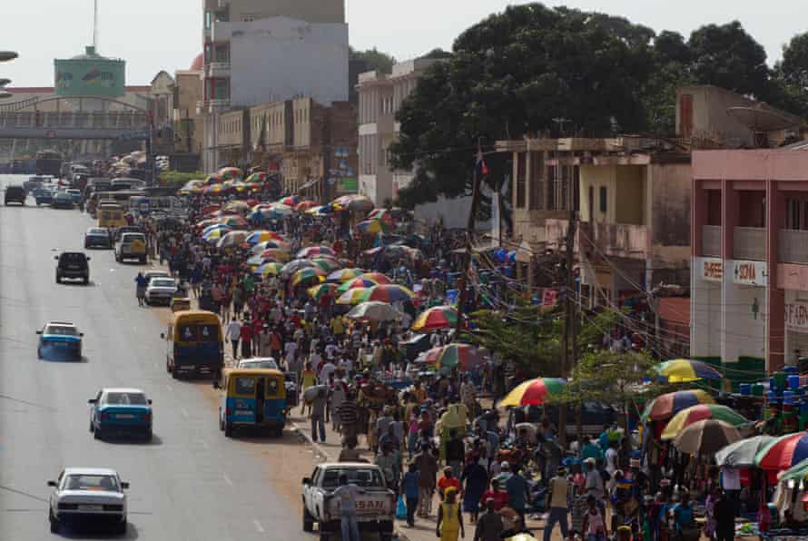 Shoppers and vendors crowd the street at Bandim Market in Bissau. Political instability makes challenging the country's reputation as a narco state difficult.