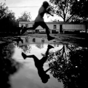 A young boy jumps over a water puddle in front of the Coffey residence after a rainstorm in Duncan, September 2009