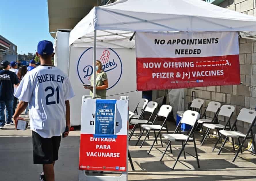 Un bărbat într-o pălărie și tricou din Los Angeles Dodgers trece pe lângă un cort cu semne care oferă bilete gratuite pentru fiecare vaccin luat înainte de joc.