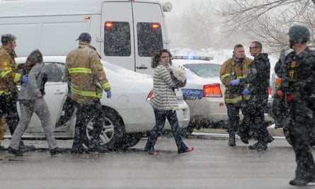People are escorted away from the scene by police after a gunman opened fire at a Planned Parenthood facility on Friday.