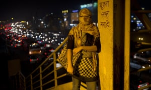 An woman has her face covered to protect from pollution and dust in Delhi, India