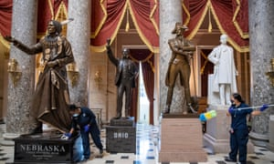 A cleaning crew dusts residue from the pedestals of the statues in Statuary Hall inside the US Capitol in Washington.