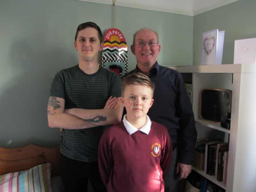 Robbie at home in his bedroom with his father and son