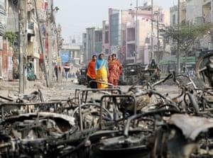 Women walk past charred vehicles in Delhi, India, 27 February