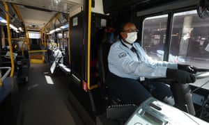 JaVita Brown, a Detroit bus driver, wears gloves and a mask while driving her route during the Covid-19 outbreak.