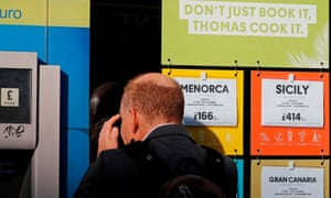 A man looks through the window of a closed branch of a Thomas Cook travel agent's shop