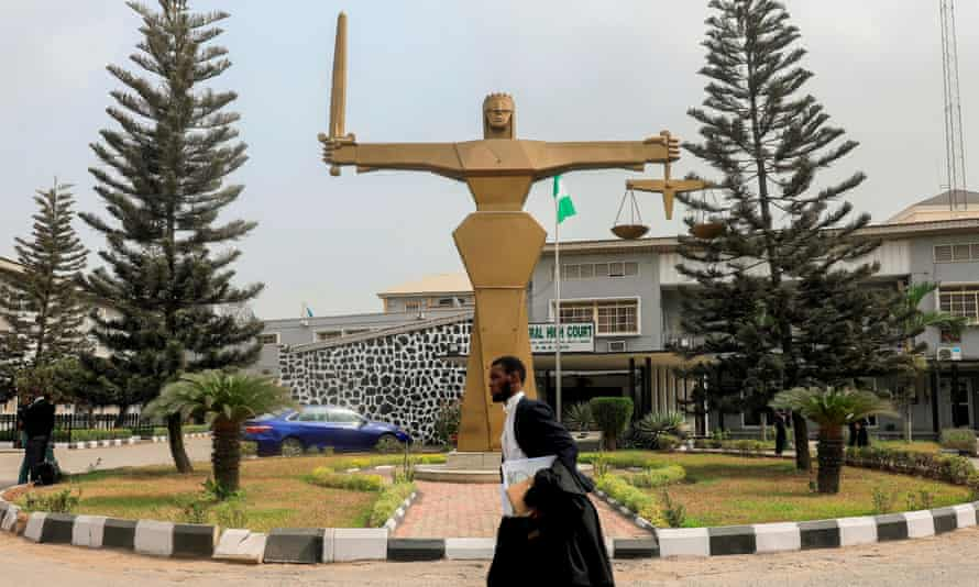 A barrister walks past the statue of Lady Justice in front of the Federal High Court in Lagos, Nigeria.