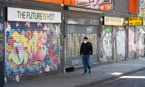Masked man walks past parade of shuttered shops