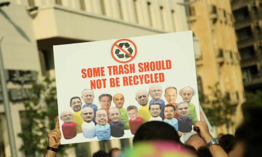A demonstrator on Saturday holds up a poster showing Lebanese politicians.