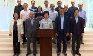 Carrie Lam stands with her cabinet as she delivers a video message released to media organisations in Hong Kong