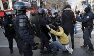 A striking worker is grabbed by police outside Gare de Lyon in Paris, France