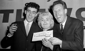 Viv Nicholson and her husband, Keith (left), are presented with the cheque by the entertainer Bruce Forsyth in 1961 after winning the football pools.