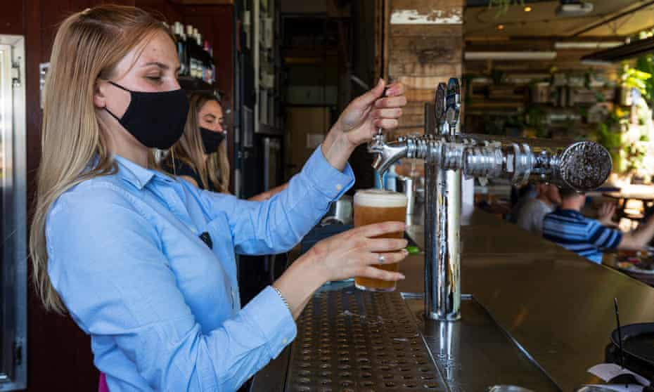 Bar staff are seen pulling a beer at College Lawn Hotel in Prahran on October 28, 2020 in Melbourne, Australia. (Photo by Daniel Pockett/Getty Images)