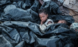 Children sleeping under sheets of plastic in Buzi, Mozambique
