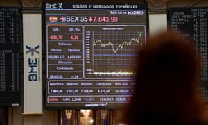 A woman looks at a screen showing the Ibex 35 stock market index at Spain's stock exchange in Madrid