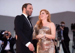 A man in a tuxedo and a woman in a gold evening gown