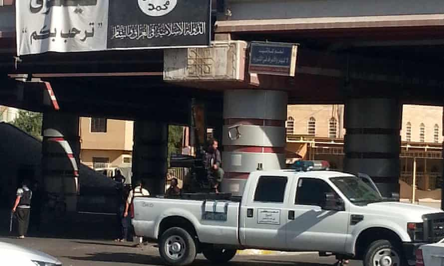 An Isis fighter mans an anti-aircraft gun mounted on the rear of a vehicle in Mosul, taken in July.