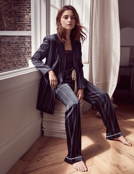 Jenna Coleman sitting by a window wearing striped blazer and trousers by Loewe (harveynichols.com) and camisole by eresparis.com.