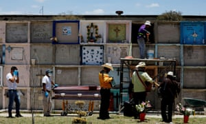 Funeral workers stand by the coffin of a woman who died of coronavirus , as musicians stand next to them at the Municipal cemetery in Nezahualcoyotl, State of Mexico, Mexico 12 June, 2020.