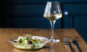 Plate of seafood and a glass of white wine on a table at Plateau, Brighton