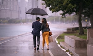 A still from the show showing a couple walking in the rain