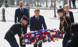 France's President Emmanuel Macron helps lay a wreath of flowers at the Arc de Triomphe in Paris.