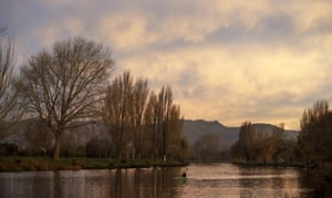 A woman paddles a kayak on the Avon River at sunset in Christchurch, New Zealand